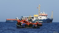 Crew members from the German NGO migrant rescue vessel Sea-Watch 3 distribute life jackets to migrants in a small wooden boat in international waters off the coast of Libya, in the western Mediterranean Sea, Aug. 1, 2021.