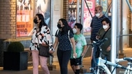 Masked people walk past posters advertising theater shows as the U.S. registers a surge in infections with the highly transmissible delta variant of the coronavirus, in New York City, July 30, 2021.