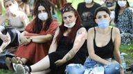 Women wearing protective masks look on during a protest organised by Ankara Women's Platform in Ankara, on July 26, 2020, in…