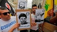 Protesters carry signs showing the faces of Lebanee Shiite movement Hezbollah leader Hassan Nasrallah and slain military…