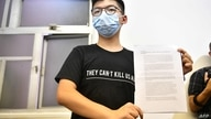 Hong Kong pro-democracy activist Joshua Wong holds up his notice for disqualification at a press conference in Hong Kong on…