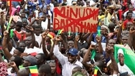 A man holds a banner against the United Nations Multidimensional Integrated Stabilization Misiion in Mali (MINUSMA) and…