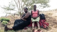Relatives of missing miners sit in the shade as they await feedback and watch progress of rescue workers busy at work…