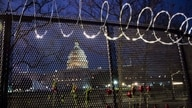 WASHINGTON, DC - JANUARY 15: Flowers are placed along the razor wire fencing that now surrounds the US Capitol on January 15,…