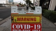 LOS ANGELES, CALIFORNIA - JANUARY 22: A sign reading 'COVID-19 High-Risk Area' is posted on a downtown sidewalk amid a surge in…
