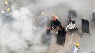 TOPSHOT - Protesters react as they are engulfed by tear gas fired by police, and as other demonstrators let off fire…