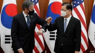 US Secretary of State Antony Blinken (L) bumps elbows with South Korean Foreign Minister Chung Eui-yong after an initialing…