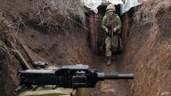 TOPSHOT - An Ukrainian serviceman walks in a trench as he stands at his post on the frontline with Russia backed separatists…