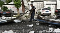 A man cleans up damage after a tornado hit the city of Suzhou in China's eastern Jiangsu province province on May 15, 2021. …