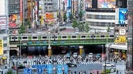 This general view shows people crossing the street as trains leave nearby Shinjuku station in Tokyo on June 17, 2021, after…