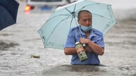 TOPSHOT - This photo taken on July 20, 2021 shows a man wading through flood waters along a street following heavy rains in…