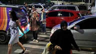 FILE - People cross a road during a rush hour traffic in Jakarta, Indonesia, March 29, 2019. Indonesia's air quality has deteriorated from among the cleanest in the world to one of the most polluted over the past two decades.
