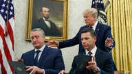 President Donald Trump, walks to acting Department of Homeland Security Secretary Kevin McAleenan, seated right, and Guatemalan Interior Minister Enrique Degenhart in the Oval Office of the White House, July 26, 2019.
