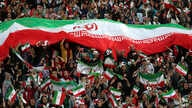 Iranian women cheer as they hold a huge Iranian flag during a soccer match between their national team and Cambodia in the 2022…
