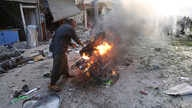 A man tries to put out a fire after a car bomb exploded in Tal Abyad, Syria, Friday, Nov. 2, 2019. A car bomb exploded in a…