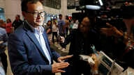 Cambodia's exiled opposition leader Sam Rainsy, left, speaks to the media as he arrived at Kuala Lumpur International's Airport…