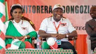 Burundi Army Gen. Evariste Ndayishimiye, center, is accompanied by his wife Angeline Ndayubaha, left, after he was chosen as…