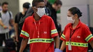 Airport employees wear masks as a precaution against the spread of the new coronavirus COVID-19 as they work at the Sao Paulo…
