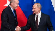 Russian President Vladimir Putin, right, and Turkish President Recep Tayyip Erdogan shake hands during a news conference after…