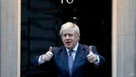 Britain's Prime Minister Boris Johnson shows thumbs up before he applauds on the doorstep of 10 Downing Street in London during…