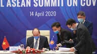 Vietnamese Prime Minister Nguyen Xuan Phuc, left, and his staff prepare documents ahead of the Special ASEAN summit on COVID-19…
