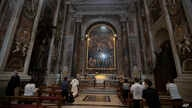 People wearing face masks to prevent the spread of COVID-19 pray in John Paul II chapel in St. Peter's Basilica at the Vatican…
