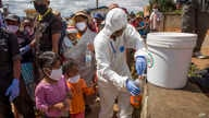In this photo taken Friday, April 24, 2020 residents are given bottles of a herbal mixture which is said to prevent and cure…