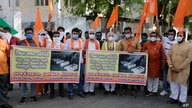 Supporters of Vishwa Hindu Parishad, or World Hindu Council, hold posters showing coffins of Indian army soldiers killed in…