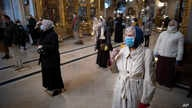 Parishioners wearing face masks to protect against coronavirus, observe social distancing guidelines cross themselves as they…