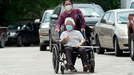 A woman is pushed in her wheelchair after being tested at a free COVID-19 testing site, provided by United Memorial Medical…