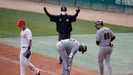 FILE - In this Tuesday, May 5, 2020, file photo, first base umpire Lee Ki-joong, wearing a mask and gloves as a precaution…