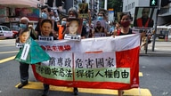 Pro-democracy demonstrators hold up a banner and portraits of jailed Chinese civil rights activists, lawyers and legal…