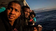 Nigerian men who were rescued off the Libyan coast on Friday, watch the sea from the deck of the Open Arms rescue vessel as the…