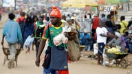 A man wearing a Cameroon soccer jersey walk past a busy Mokolo Market in Yaounde, Cameroon, Thursday Oct. 11, 2018. Cameroon…