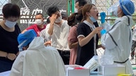 Residents line up to get tested at a coronavirus testing center set up outside a sports facility in Beijing, Tuesday, June 16,…