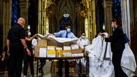 Organizers cover the boxed cremated remains of Mexicans who died from COVID-19 before a service at  St. Patrick's Cathedral,…