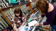 Andrea Schry, right, fills out the buyer part of legal forms to buy a handgun as shop worker Missy Morosky fills out the…