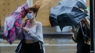 Pedestrians struggle to control their umbrellas due to inclement weather brought about by Tropical Storm Fay, Friday, July 10,…
