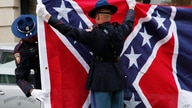 A Mississippi Highway Safety Patrol honor guard folds the retired Mississippi state flag after it was raised over the Capitol…
