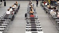 Students sit at tables in a hall at KoelnMesse exhibition grounds and wait for beginning of exams, in Cologne, Germany, Tuesday…
