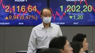 A currency trader passes by screens showing Korea Composite Stock Price Index (KOSPI), left, and foreign exchange rate at the…