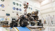 In this Dec. 17, 2019 photo made available by NASA, engineers watch the first driving test for the Mars 2020 rover in a clean…