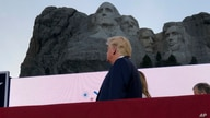 President Donald Trump watches as planes perform fly-overs of the Mount Rushmore National Monument Friday, July 3, 2020, in…