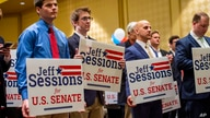 Jeff Sessions supporters hold campaign signs as they listen to his speech at his watch party following Alabama's state primary,…