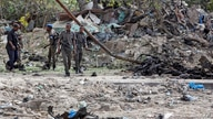 Somali soldiers attend the scene where a suicide car bomber detonated near the gates of the motor vehicle imports duty…