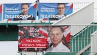 A man walks by campaign posters showing two contenders in Poland's presidential election runoff to be held Sunday, conservative…