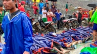 People gather near the bodies of victims of a landslide near a jade mining area in Hpakant, Kachine state, northern Myanmar…