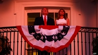 President Donald Trump and first lady Melania Trump stand on the Truman Balcony of the White House as they watch a fireworks…