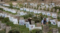Yemeni men offer prayers at the grave of their relative who was killed during Yemen's ongoing conflict, at a cemetery in Sanaa,…