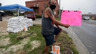 Michael Bledsoe sells sandbags as Tropical Storm Isaias approaches in Wilmington, N.C., Monday, Aug. 3, 2020. (AP Photo/Gerry…